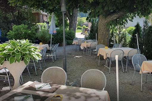 Bild der Gartenterasse mit hohen Bämen und Tischen auf einem Kiesplatz.